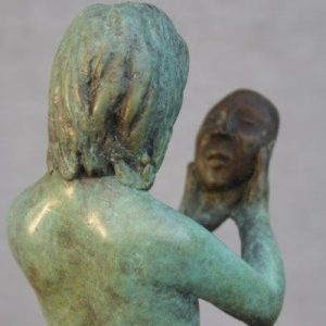 Bronze sculpture of young female looking at a mask
